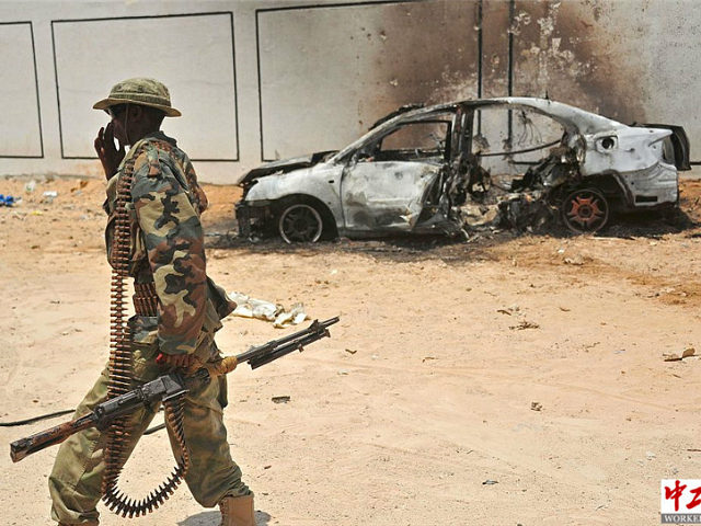 A Somali soldier patrols next to the burnt-out wreckage of a car that was used by suspected al-shabab fighters on April 16, 2017. Somali security forces shot dead two suspected al-shabab militants, an Al-Qaeda linked extremist group, who were said to be involved in firing rockets. / AFP PHOTO / …