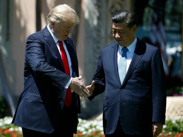 President Donald Trump and Chinese President Xi Jinping reach to shake hands at Mar-a-Lago, Friday, April 7, 2017, in Palm Beach, Fla. (AP Photo/Alex Brandon)