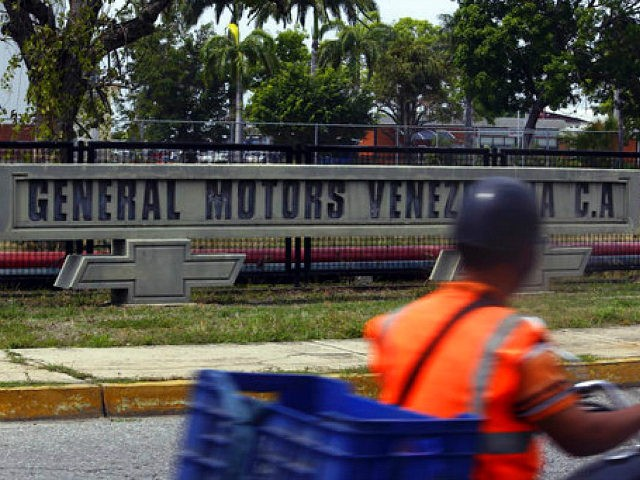 A motorcyclist rides past the General Motors' plant in Valencia, Venezuela, Thursday, April 20, 2017. The company announced that it was shuttering operations in the country after authorities seized the factory on Wednesday, April 19. General Motors' announcement comes as Venezuela's opposition looks to keep up pressure on President Nicolas Maduro, taking to the streets again Thursday after three people were killed and hundreds arrested in the biggest anti-government demonstrations in years. (AP Photo/Juan Carlos Hernandez)