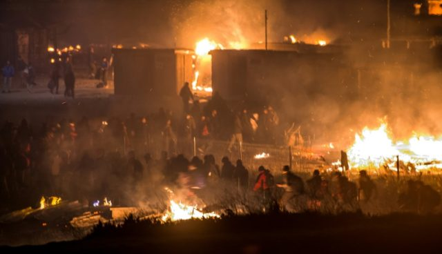 Migrants flee as a huge fire destroys the Grande-Synthe camp outside the northern French city of Dunkirk
