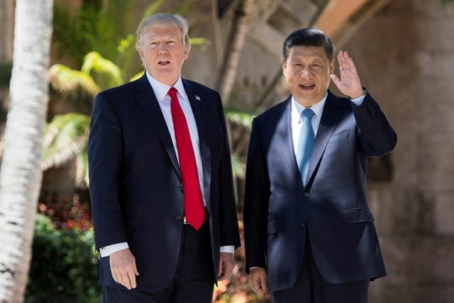 Chinese President Xi Jinping (right) waves to the press as he walks with US President Donald Trump at the Mar-a-Lago estate in West Palm Beach, Florida, April 7, 2017
