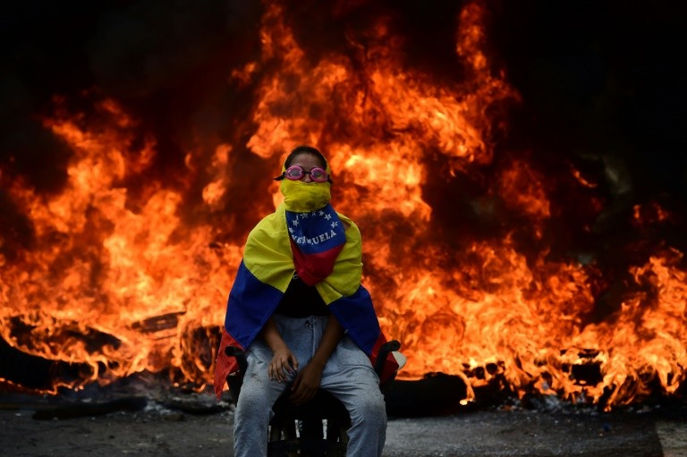 A Venezuelan opposition activist is backdropped by a burning barricade during a demonstration against President Nicolas Maduro in Caracas, on April 24, 2017