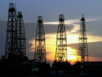 FILE - In this Aug. 1, 2004 file photo, the sun sets behind an oil drilling rig near Cabimas, Venezuela. The falling oil prices in 2014 that are providing relief to drivers around the world threaten to bring more misery to millions of Venezuelans, whose country depends almost exclusively on …