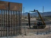 In this March 30, 2017 file photo, Workers use a crane to lift a segment of a new fence into place on the U.S. side of the border with Mexico, where Sunland Park, New Mexico, meets the Anapra neighborhood of Ciudad Juarez, Mexico, As President Donald Trump's administration fights to fund a new, multibillion-dollar border wall, government lawyers are still settling claims with Texas landowners over the fence Congress approved more than a decade ago.