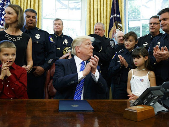 President Donald Trump claps in the Oval Office of the White House in Washington, Monday, May 15, after after signing a law enforcement executive order. The president is asking the Justice Department to develop strategies to prevent and prosecute violent crimes against law enforcement. (AP Photo/Evan Vucci)