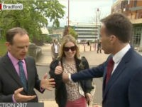 A BBC reporter tried to push aside a woman who interrupted him in the middle of a live, on-camera interview and wound up grabbing her breast.