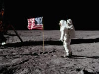 Astronaut Buzz Aldrin stands next to the deployed United States flag during the Apollo II lunar landing mission, 1969.