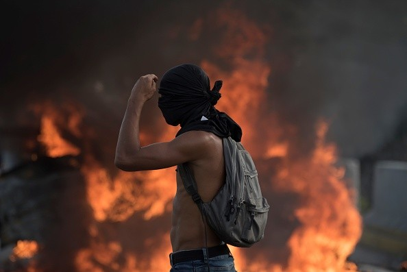 CARACAS, VENEZUELA - APRIL 24: Venezuelan opposition activist cover his face in front of burning barricades as the protesters block a main highway during a march against the government of President NIcolas Maduro, in Caracas, on April 24, 2017. Venezuela is grappling with a new wave of political protest since …