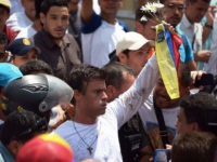 Leopoldo Lopez, an ardent opponent of Venezuela's socialist government facing an arrest warrant after President Nicolas Maduro ordered his arrest on charges of homicide and inciting violence, is escorted by the National Guard after turning himself in, during a demonstration in Caracas on February 18, 2014. Fugitive Venezuelan opposition leader …