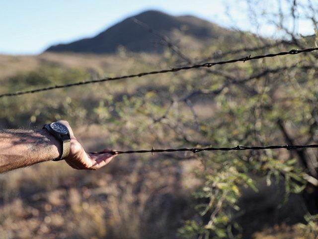 ARIVACA, AZ - NOVEMBER 14: A civilian paramilitary with Arizona Border Recon lifts a barbed wire fence at the U.S.-Mexico border on November 14, 2016 near Arivaca, Arizona. The armed group, made up mostly of former U.S. military servicemen and women, stages reconnaissance and surveillance operations against drug and human …