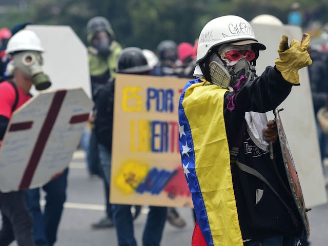 Demonstrators clash with police as they march during a protest against Venezuelan President Nicolas Maduro, in Caracas on May 3, 2017. Venezuela's angry opposition rallied Wednesday vowing huge street protests against President Nicolas Maduro's plan to rewrite the constitution and accusing him of dodging elections to cling to power despite …