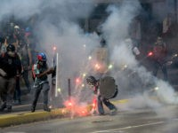 TOPSHOT - Demonstrators clash with riot police during a protest against the government of President Nicolas Maduro in Caracas on May 20, 2017. Venezuelan protesters and supporters of embattled President Nicolas Maduro take to the streets Saturday as a deadly political crisis plays out in a divided country on the …