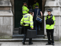 Police officers carry cases into Granby House following a raid, close to Manchester Piccadilly railway station in Manchester, on May 24, 2017, as their investigations continue into the May 22 terror attack at the Manchester Arena.