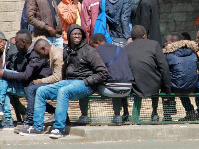 Migrant men outside of the makeshift migrant camp at Port de La Chapelle in Paris, France.
