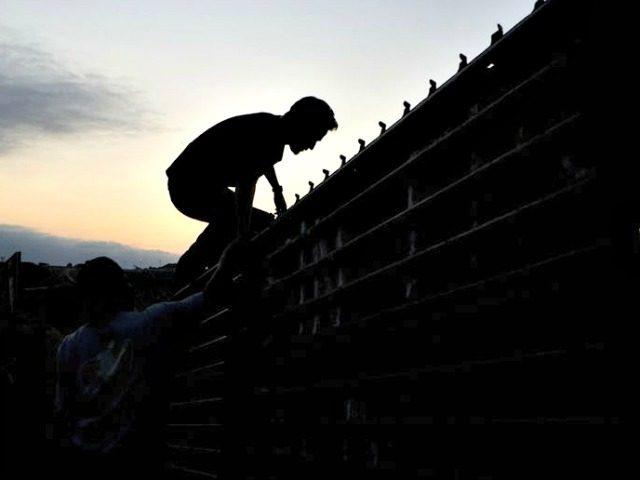 Man Climbs Border Fence AP