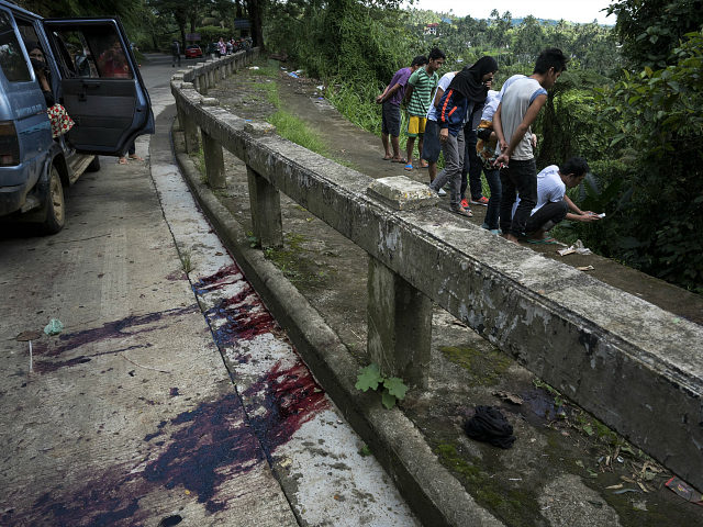 MARAWI CITY, PHILIPPINES - MAY 28: Residents view unidentified bodies believed to be executed by armed militants and dumped in a ditch as blood stains are seen on the pavement of a road on May 28, 2017 in Marawi city, southern Philippines. The 8 men, who were hogtied and executed …