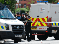 Police officers work at the scene near a property they entered in the Moss Side area of Manchester on May 27, 2017 during an operation. British police said they arrested two more people during raids Saturday in connection with the suicide bombing at a Manchester concert, with a 'large part' …