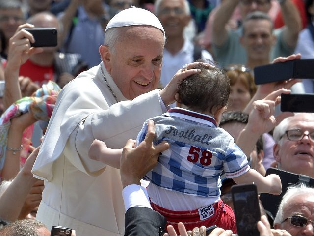 Pope Francis blesses a child as he leaves in his papamobile after the Holy mass with the ecclesial movements for Pentecost Sunday on May 19, 2013 at St peter's square at the Vatican. AFP PHOTO / ANDREAS SOLARO (Photo credit should read ANDREAS SOLARO/AFP/Getty Images)