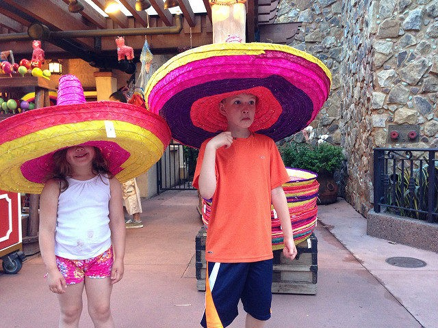 Two children trying on oversize sombreros