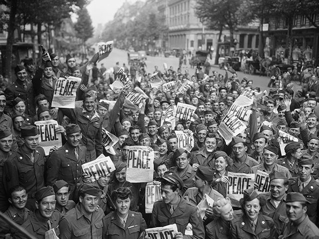 """""""American servicemen and women gather in front of 'Rainbow Corner' Red Cross club in Paris to celebrate the unconditional surrender of the Japanese"""" By McNulty, August 15, 1945 (Source: National Archives)"""