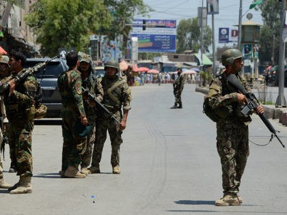 Afghan security forces stand at the site of suicide bombing in Jalalabad on May 17, 2017. Suicide bombers stormed the national television station in the eastern Afghan city of Jalalabad on May 17, triggering gunfights and explosions as journalists remained trapped inside the building, officials and eyewitnesses said. At least …