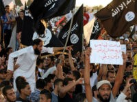 Supporters of the Jihadist group Ansar al-Sharia shout religious slogans while holding Al-Qaeda-affiliated flags to counter a demonstration by thousands of people against militias in the eastern city of Benghazi on September 21, 2012. Thousands of Libyans rallied against militias in the tense city of Benghazi, drowning out a protest by radical Salafists furious over a film and cartoons deemed offensive to Islam. Sign (R) reads 'Long live free Libya. We want a national army and security.' AFP PHOTO/ABDULLAH DOMA (Photo credit should read ABDULLAH DOMA/AFP/Getty Images)