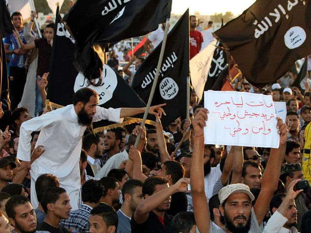 Supporters of the Jihadist group Ansar al-Sharia shout religious slogans while holding Al-Qaeda-affiliated flags to counter a demonstration by thousands of people against militias in the eastern city of Benghazi on September 21, 2012. Thousands of Libyans rallied against militias in the tense city of Benghazi, drowning out a protest …