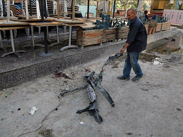 A man clears debris from the aftermath of a massive bombing in central Baghdad, Iraq, Monday, May 30, 2017. The bomb exploded outside a popular ice cream shop in the Karrada neighborhood of Baghdad just after midnight on Monday, killing and wounding dozens of civilians, hospital and police officials said. …
