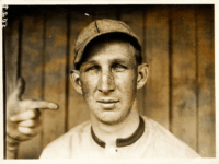 "Portrait of ""Harvard Eddie"" Edward Leslie Grant, third baseman for the Cincinnati Reds, head-and-shoulders portrait, facing front, with another person's left hand and index finger pointing at Eddie's head. The photo is captioned ""Grant, Phila. Nat."", but photographer Paul Thompson may have been unaware that Grant began the 1911 season …"