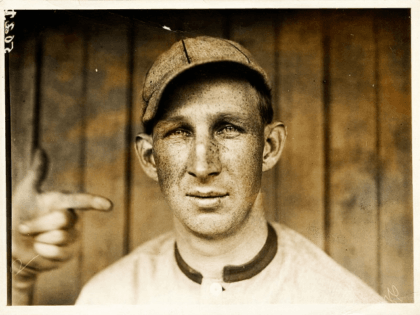 """Portrait of """"Harvard Eddie"""" Edward Leslie Grant, third baseman for the Cincinnati Reds, head-and-shoulders portrait, facing front, with another person's left hand and index finger pointing at Eddie's head. The photo is captioned """"Grant, Phila. Nat."""", but photographer Paul Thompson may have been unaware that Grant began the 1911 season …"""
