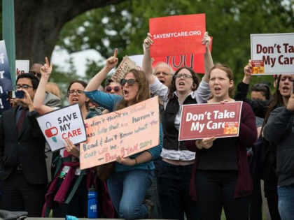 Protesters hold signs and shout at lawmakers walking out of the US Capitol in Washington, DC, on May 4, 2017 after the House of Representatives narrowly passed a Republican effort to repeal and replace Obamacare, delivering a welcome victory to President Donald Trump after early legislative stumbles. Following weeks of …