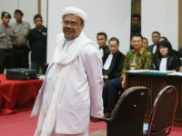Indonesian firebrand cleric Rizieq Shihab (front) prepares to take his seat in court to testify in the blasphemy trial of Jakarta's Christian governor Basuki Tjahaja Purnama (background 2nd R), also known as 'Ahok', in Jakarta on February 28, 2017. Jakarta's Christian governor is currently standing trial for blasphemy as he heads for a tough run-off against a Muslim opponent in city elections seen as a test of religious tolerance in Muslim-majority Indonesia. / AFP / POOL / RAMDANI (Photo credit should read RAMDANI/AFP/Getty Images)