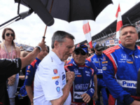 Japanese driver Takuma Sato (C) is greeted on the starting grid of the 101st Indy 500 by former US driver Johnny Rutherford, who won the race three times