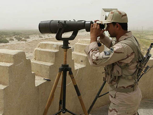 An Iranian border guard looks through a pair of binoculars to monitor a border area for drug trafficking activities on July 19, 2011, in Milak, southeastern Iran. The region borders both Aghanistan and Pakistan, and sits on a major trafficking route. The UN office on drugs and crime (UNODC) today …