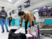 A Libyan traveller packs his laptop in his suitcase before boarding his flight for London at Tunis-Carthage International Airport on March 25, 2017. The United States this week announced a ban on all electronics larger than a standard smartphone on board direct flights out of eight countries across the Middle …