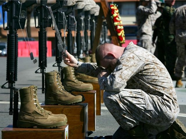 Corporal William Ward, a combat correspondent with the 1st Battalion, 1st Marines, holds the dog tags of fallen companions as the Marines of Regimental Combat Team 5 (RCT-5 ) memorialize 100 Marines, soldiers, and sailors who died during the regiment's 12-month deployment to fight in the Al Anbar Province of Iraq on February 15, 2007 at Camp Pendleton, California. The RCT-5 was assigned to cultivate the combat capabilities of the Iraqi Security Forces in the greater Fallujah region and helped facilitate the expansion of the 2nd Brigade, 1st Iraqi Division's battlespace in Fallujah proper and saw the repositioning of Marines to the edges of the city. (Photo by David McNew/Getty Images)