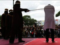 BANDA ACEH, INDONESIA - MAY 23: An Indonesian man gets caning in public from an executor known as 'algojo' for having gay sex, which is against Sharia law at Syuhada mosque on May 23, 2017 in Banda Aceh, Indonesia. The two young gay men, aged 20 and 23, were caned …