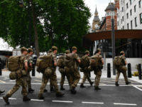 British soldiers arrive by bus and head toward a building next to New Scotland Yard police headquarters near to the Houses of Parliament in central London on May 24, 2017