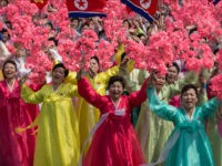 Women wearing traditional Korean dress wave flowers and shout slogans as they pass North Korea's leader Kim Jong-Un during a mass rally marking the 105th anniversary of the birth of late North Korean leader Kim Il-Sung in Pyongyang on April 15, 2017. North Korean leader Kim Jong-Un on April 15 …