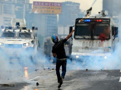 TOPSHOT - Opposition activists and riot police clash during a protest against President Nicolas Maduro, in Caracas on May 8, 2017. Venezuela's opposition mobilized Monday in fresh street protests against President Nicolas Maduro's efforts to reform the constitution in a deadly political crisis. Supporters of the opposition Democratic Unity Roundtable …