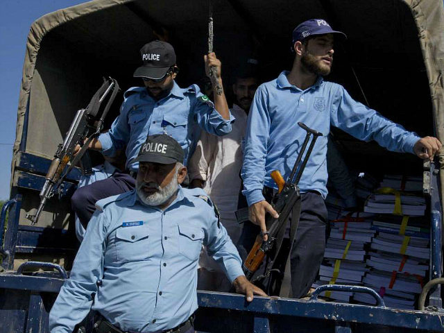 Pakistani police officers stand guard on a truck carries copies of budget 2017-18, arrived at the Parliament in Islamabad, Pakistan, Friday, May 26, 2017. Pakistan's Finance Minister introduced a $50 billion development-heavy budget that also promises a 7 per cent increase in military spending. (AP Photo/B.K. Bangash)