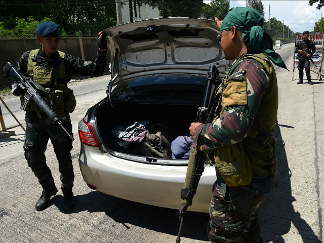 Philippine policemen check a car boot of a resident fleeing from Marawi city, where gunmen who had declared allegiance to the Islamic State group rampaged through the southern city, at a checkpoint in Iligan City, in southern island of Mindanao on May 24, 2017. Philippine President Rodrigo Duterte warned that …