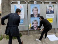 Members of French far-right party Front National Youth Movement (FNJ) party stick posters of French far-right Front National (FN) party candidate for the presidential election Marine Le Pen on April 27, 2017 in Ajaccio, on the French Mediterranean island of Corsica. / AFP PHOTO / PASCAL POCHARD-CASABIANCA (Photo credit should …