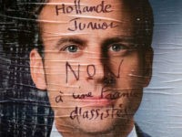 An electoral poster of French presidential election candidate for the En Marche ! movement Emmanuel Macron is covered with a graffiti reading 'Hollande Junior, no to a France of assisted people' in Paris, on May 2, 2017. / AFP PHOTO / JOEL SAGET (Photo credit should read JOEL SAGET/AFP/Getty Images)