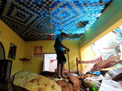 A Sri Lankan mudslide survivor salvages belongings at a destroyed house in Kiribathgala, in Ratnapura district, Sri Lanka, Monday, May 29, 2017. (AP Photo/Eranga Jayawardena)