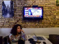 A woman follows the referendum results on television near Taksim square in Istanbul on April 16, 2017. The 'Yes' campaign to give Turkish President expanded powers was just ahead in a tightly-contested referendum but the 'No' was closing the gap, according to initial results. / AFP PHOTO / YASIN AKGUL …