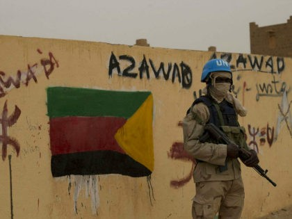 FILE - In this Sunday, July, 28, 2013 file photo, a United Nations peacekeeper stands guard at the entrance to the main polling station, covered in separatist flags and graffiti supporting the creation of the independent state of Azawad, in Kidal, Mali. Mali's new president-elect Ibrahim Boubacar Keita, whose rival …