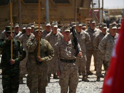 US Marines and Afghan National Army (ANA) soldiers carry flags during a handover ceremony at Leatherneck Camp in Lashkar Gah in the Afghan province of Helmand on April 29, 2017. US Marines returned to Afghanistan's volatile Helmand April 29, where American troops faced heated fighting until NATO's combat mission ended …