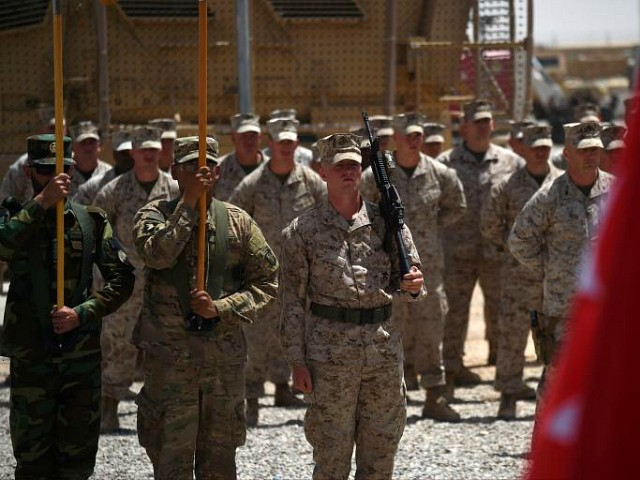 US Marines and Afghan National Army (ANA) soldiers carry flags during a handover ceremony at Leatherneck Camp in Lashkar Gah in the Afghan province of Helmand on April 29, 2017. US Marines returned to Afghanistan's volatile Helmand April 29, where American troops faced heated fighting until NATO's combat mission ended in 2014, as embattled Afghan security forces struggle to beat back the resurgent Taliban. The deployment of some 300 Marines to the poppy-growing southern province came one day after the militants announced the launch of their 'spring offensive', and as the Trump administration seeks to craft a new strategy in Afghanistan. / AFP PHOTO / WAKIL KOHSAR (Photo credit should read WAKIL KOHSAR/AFP/Getty Images)