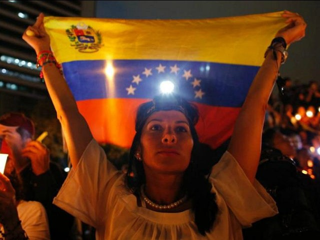 A demonstrator holds a Venezuelan flag during a vigil for the victims of the clashes with the government's security forces, during protest against President Nicolas Maduro in Caracas, Venezuela, Wednesday, May 17, 2017. Several humanitarian organizations and the opposition have accused the security forces of using too much violence during …